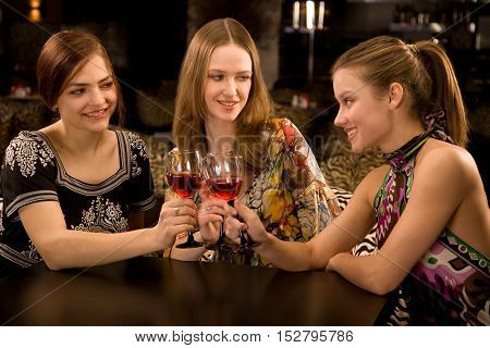 Three young woman in the nightclub are having fun and drink