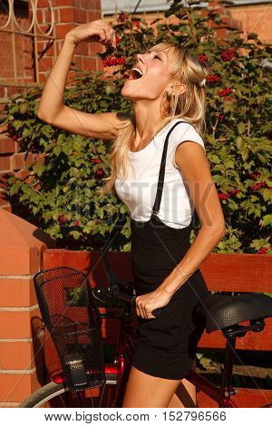 Young woman  with bicycle eating ashberry outdoors