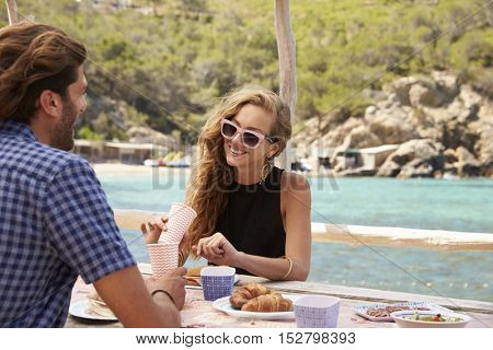 Young couple sitting at a table by the sea, looking away
