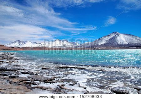 Long shot of the Laguna Verde with turquoise water, mountains in the background and a blue sunny sky in Chile, South America