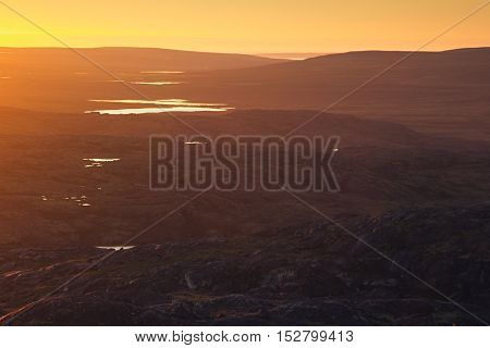 Beautiful soft sunset light over the mountain lake and valley. Arctic summer the tundra Norway.