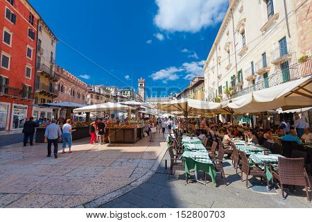 VERONA ITALY- September 08 2016: People buying fruits and vegetables on the local market and tourists in the cafe on Piazza delle Erbe (Market square) in Verona Italy.