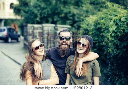 Young man hipster with handsome bearded face man hugging two pretty girls friends in sunglasses casual clothes with expressive laughing faces standing on city street background outdoor