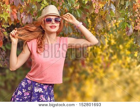 Fall Fashion. Urban Model Woman in Fashion Outfit Having Fun. Glamour Sexy Hipster Girl Smiling, fashion Trendy Hairstyle. Crazy Redhead Enjoy Autumn Nature, Stylish Sunglasses. Autumn Outdoor Park