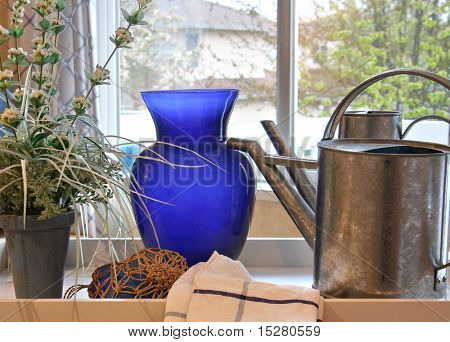 Watering can, flowers and a vase on a tray in the kitchen of a show home.