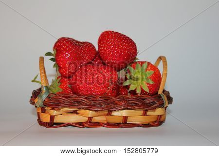 few ripe red strawberries on a white background in the basket