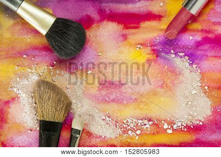 Makeup brushes and lipstick on a vibrant yellow and purple background, with traces of powder and blush. Horizontal template for makeup artist's business card or flyer design, with plenty of copyspace