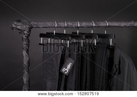 Lot Of Black Pants Jeans And Jacket Hanging On Clothes Rack.  Background. Sale Sign.  Friday. Close