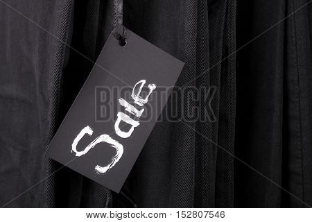 Sign Sale On Black Pants And Jeans Background. Copy Space.  Friday. Close Up.