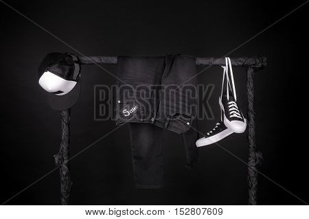 Black And White Senakers, Cap  Pant, Jeans Hanging On Clothes Rack   Background. Sale Sign.  Friday.