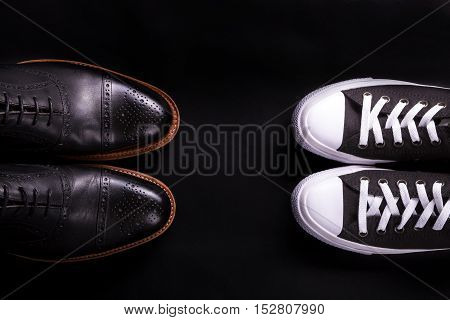 Mixed Shoes. Oxford And Sneakers Shoe On Black Background.  Different Style Of Men Fashion. Compare
