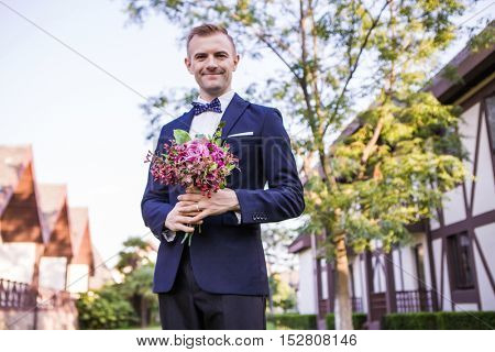 Front view of smiling groom holding bouquet at lawn