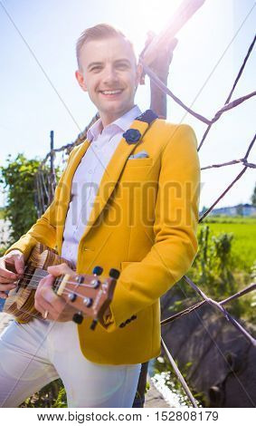 Dapper man playing with a small guitar outdoors