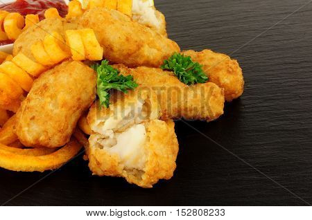 Battered cod nuggets with curly fries on a slate stone background