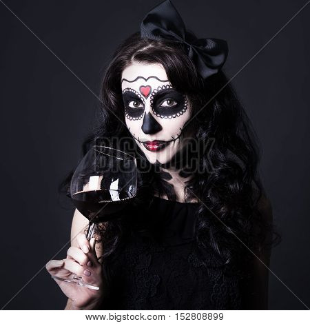 Alcohol Addiction Concept - Woman With Halloween Skull Make Up Holding Glass Of Wine Or Blood Over B