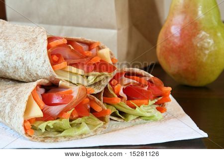 Healthy lunch, ham, cheese and vegetables wrapped in a whole wheat tortilla.