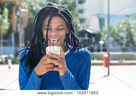 Guy with dreadlocks receiving good news outdoor in the city in the summer