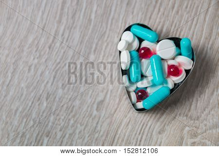 Heart From Colorful Medication And Pills  Above On Grey Wooden Background. Copy Space. Top View, Fra