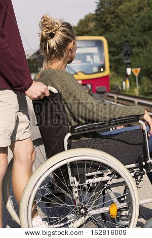 woman in wheelchair at a train station with someone helping her