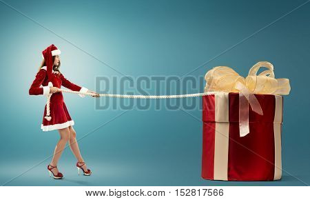 Santa woman pulling huge red gift box