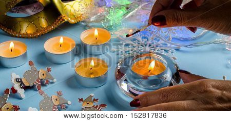 The girl's hands lit from the burning match of a candle. Dark red nail Polish. Blue background. Round candles. The twinkling lights of garlands. Carnival mask decorative figurines of deer.