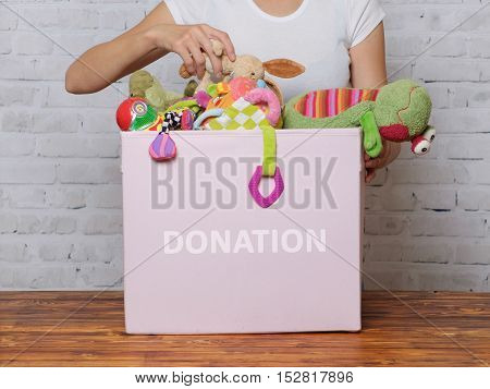Girl prepare to donate toys in charity shop