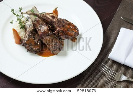 Plate with roast ribs  of lamb with potato  on color back