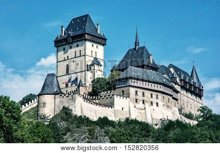 Karlstejn is a large gothic castle founded 1348 by Charles IV in Czech republic. Ancient architecture. Travel destination. Blue photo filter. Beautiful place.