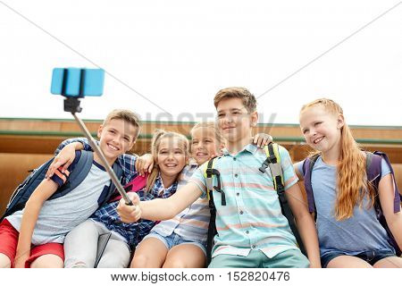 primary education, technology, friendship, childhood and people concept - group of elementary school students with backpacks sitting on bench and taking picture by smartphone selfie stick outdoors