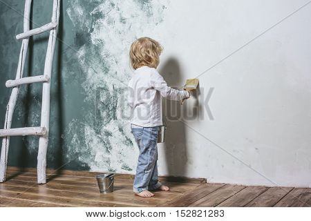 Little Beautiful And Happy Child In Jeans Paint The Wall With Brush At Home