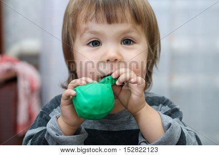 Little cute child intend to puff out ball