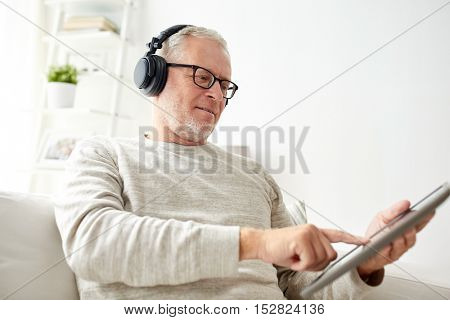 technology, old people, lifestyle and distance learning concept - happy senior man with tablet pc computer and headphones listening to music at home