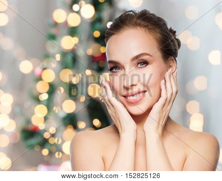 beauty, people, holidays and health concept - beautiful young woman touching her face over christmas tree lights background