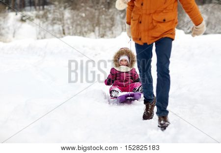 family, sledding, season and people concept - father pulling sled with happy child outdoors in winter