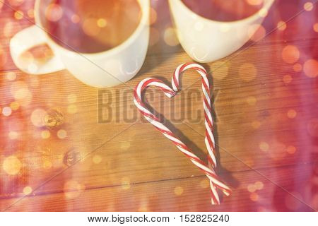 holidays, christmas, winter, food and drinks concept - close up of candy canes and cups with hot chocolate or cocoa drinks on wooden table over lights