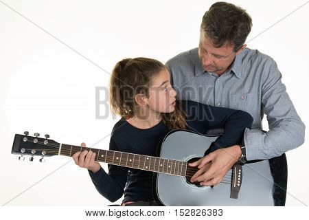 Adorable young Girl getting guitar lessons with man
