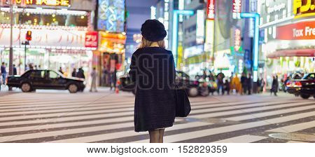 Solitary japanese woman waiting on crossroad in Kabukicho, entertainment and red-light district in Shinjuku, Tokyo, Japan.