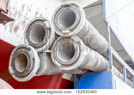 Water hose with couplings piled on the sewage truck suction or discharge hose.