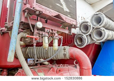 View on truck compressor water hose with couplings piled on the sewage truck suction or discharge hose.
