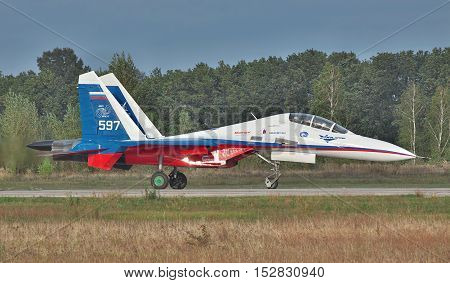 Kiev Region Ukraine - September 28 2010: Sukhoi Su-30LL fighter plane in Russian flag colors is taxiing along the runway after a training flight