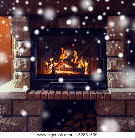 winter, christmas, warmth, fire and coziness concept - close up of burning fireplace at home with snow