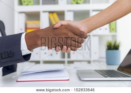 Close up of African American man shaking hand with his his female colleague in office. Concept of meeting
