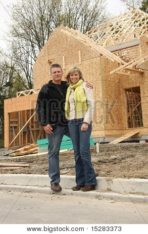 Feliz pareja delante de su casa aún en construcción.