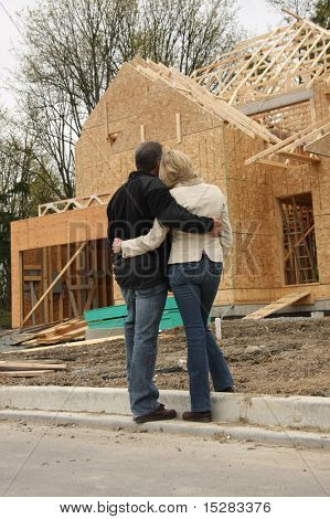 Happy couple looking at their new home still under construction.