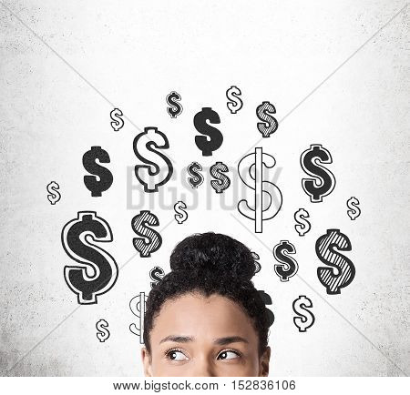 Close up of African American woman with her head surrounded by question mark sketches drawn on concrete wall. Concept of money thoughts. Mock up