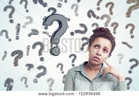African American girl standing in gray room with floating question marks in the background. Concept of decision making. Toned image