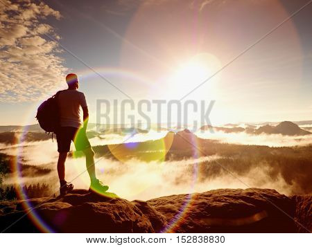 Flare. Lens Defect, Reflections. Ginger Hair Hiker In Black Pants On Cliff Above Deep Valley.