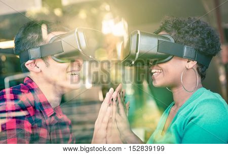 Multiracial couple in love going beyond racial diversity through virtual reality glasses - Young people having fun using new technology - Composition with window reflection on enhanced sun flare halo