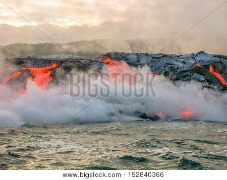 Scenic view from boat of Kilauea Volcano in Hawaii Volcanoes National Park, while erupting lava into Pacific Ocean, Big Island, Hawaii, United States.