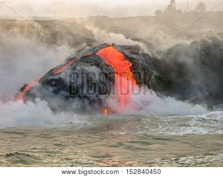 Sea view of Kilauea Volcano in Big Island, Hawaii, United States. Shot taken at sunset when the lava glows in the dark as jumps into the sea. The Kilauea erupting since 1983.